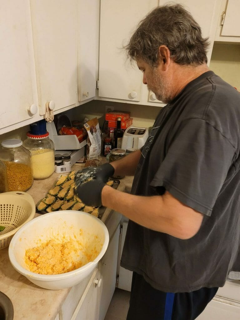 stuffing the jalpenos with cheese and wrapping in bacon