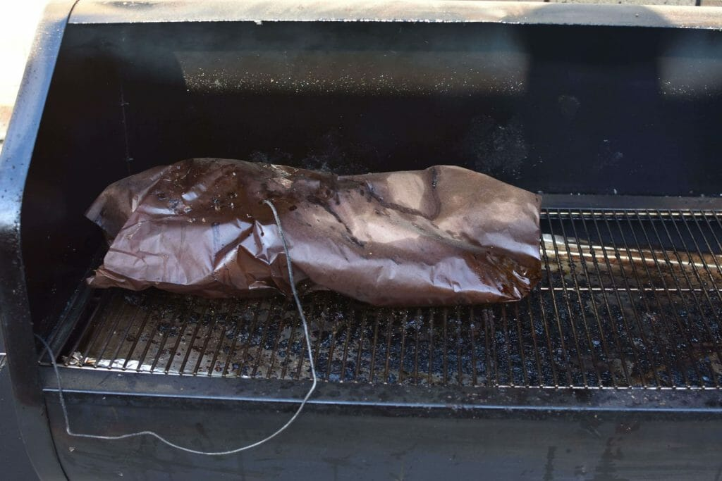boston butt wrapped with probe in on smoker with texas crutch