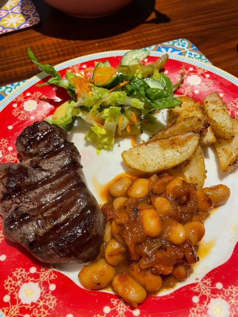 Bistec en un plato con patatas fritas, frijoles horneados y ensalada